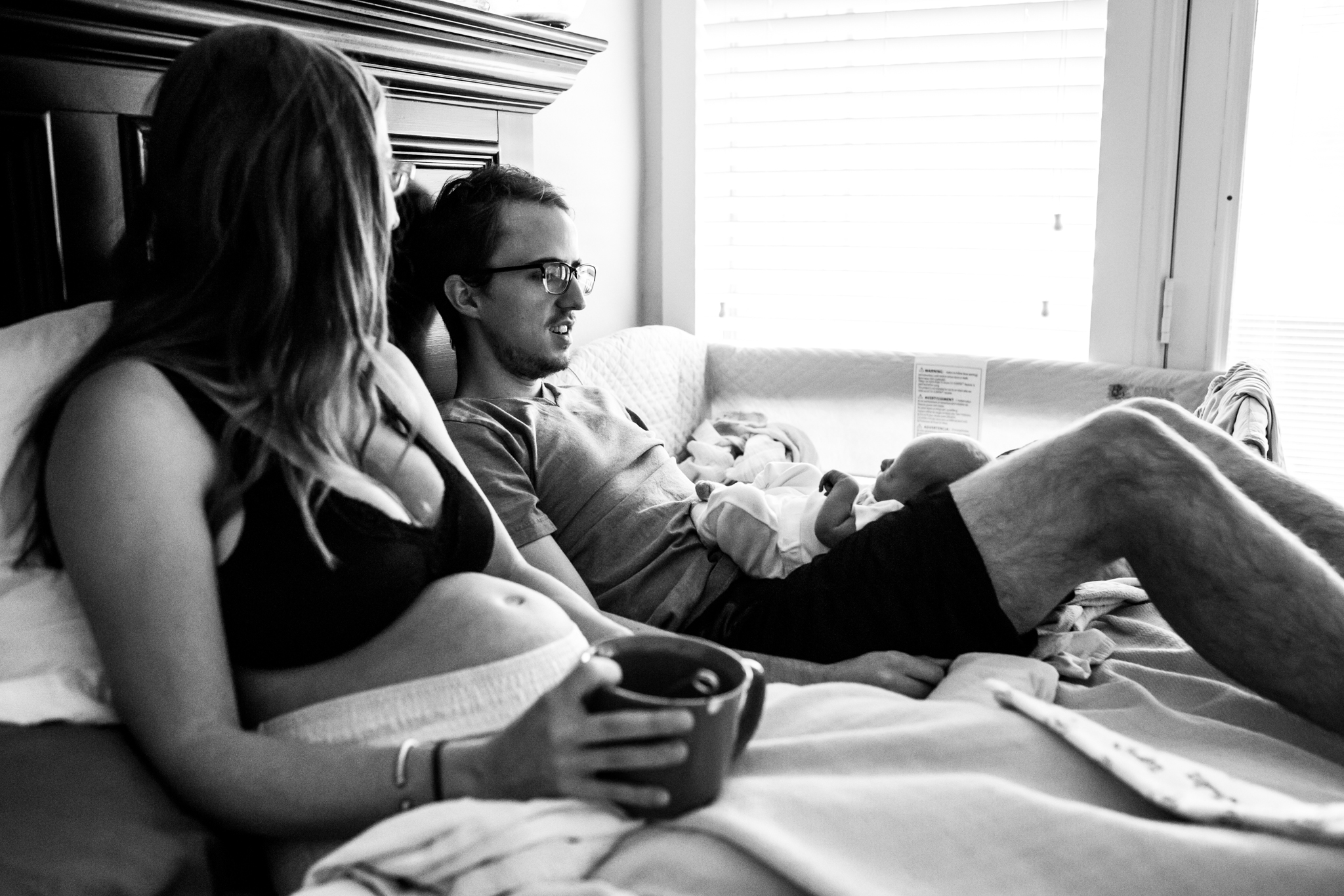 Dallas family photographer Lawren Rose Photography does a full day documentary sessions called a day in the life for a family in farmers branch, texas and takes a photo of a husband and wife lounging in bed early in the morning drinking hot tea and cuddling their 3 day old baby