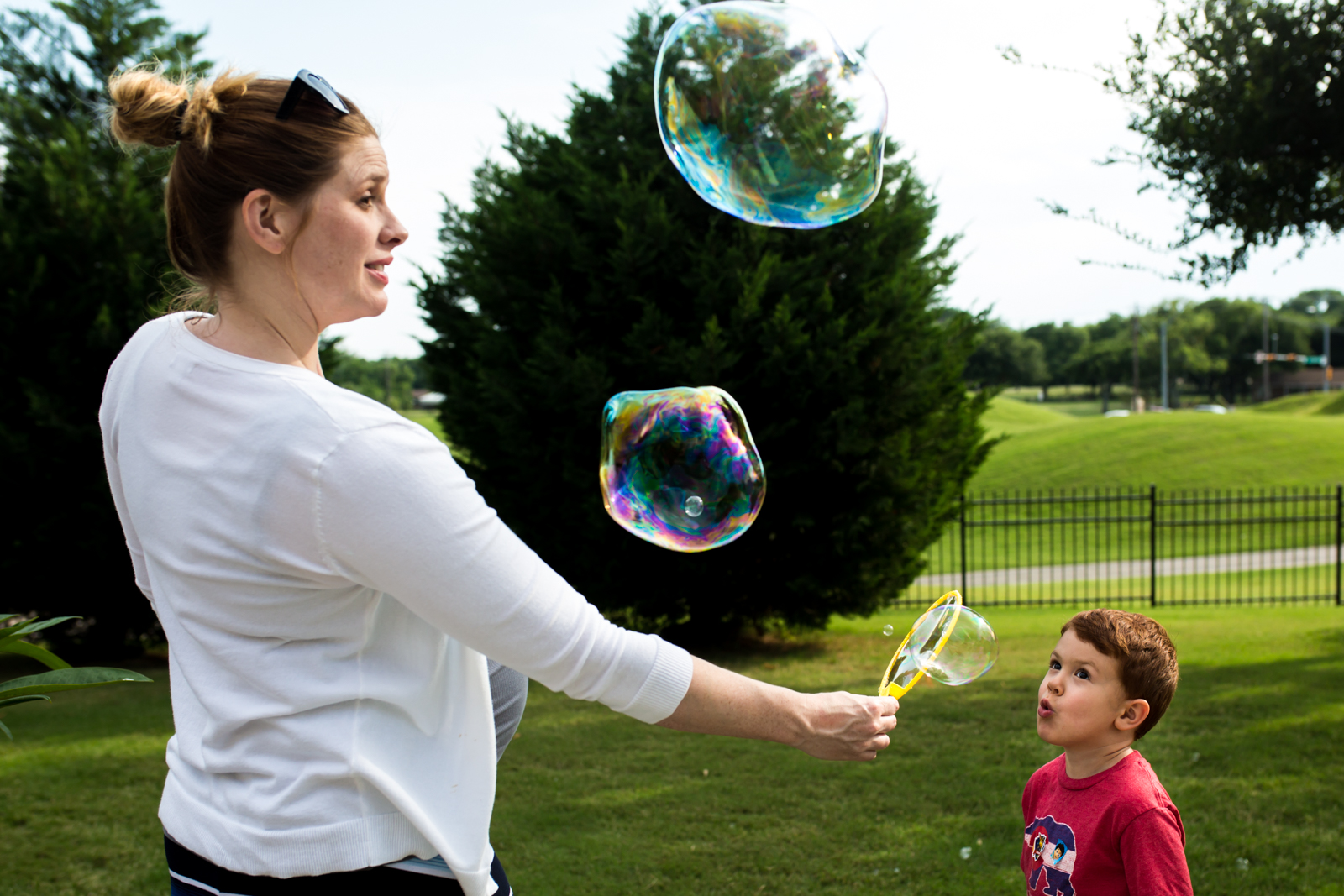 Lawren Rose Photography captures a photo of a pregnant Mom holding a bubble wand out for her 4 year old son who is blowing huge gigantic bubbles into the air