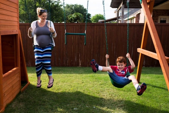 McKinney Maternity Photographer Lawren Rose Photography catches a great moment with her camera of a pregnant Mom and her redheaded son swinging on a swing set in their backyard