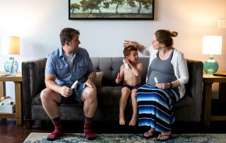 Lawren Rose Photography takes a family portrait of a pregnant Mom, Father, and their 4 year old son sitting on a couch eating popsicles in a McKinney Texas home