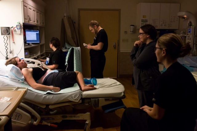 Lawren Rose Photography takes a photograph of a laboring Mom in a hospital bed with the nurses and birth team surrounding the bed at Baylor University Medical Center in Dallas Texas