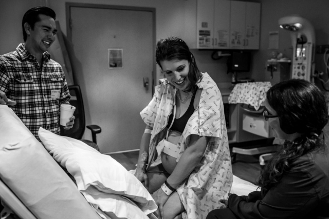 Lawren Rose Photography catches photo of a laboring mom laughing between contractions with her husband and midwife at the Baylor University Medical Center in Dallas Texas
