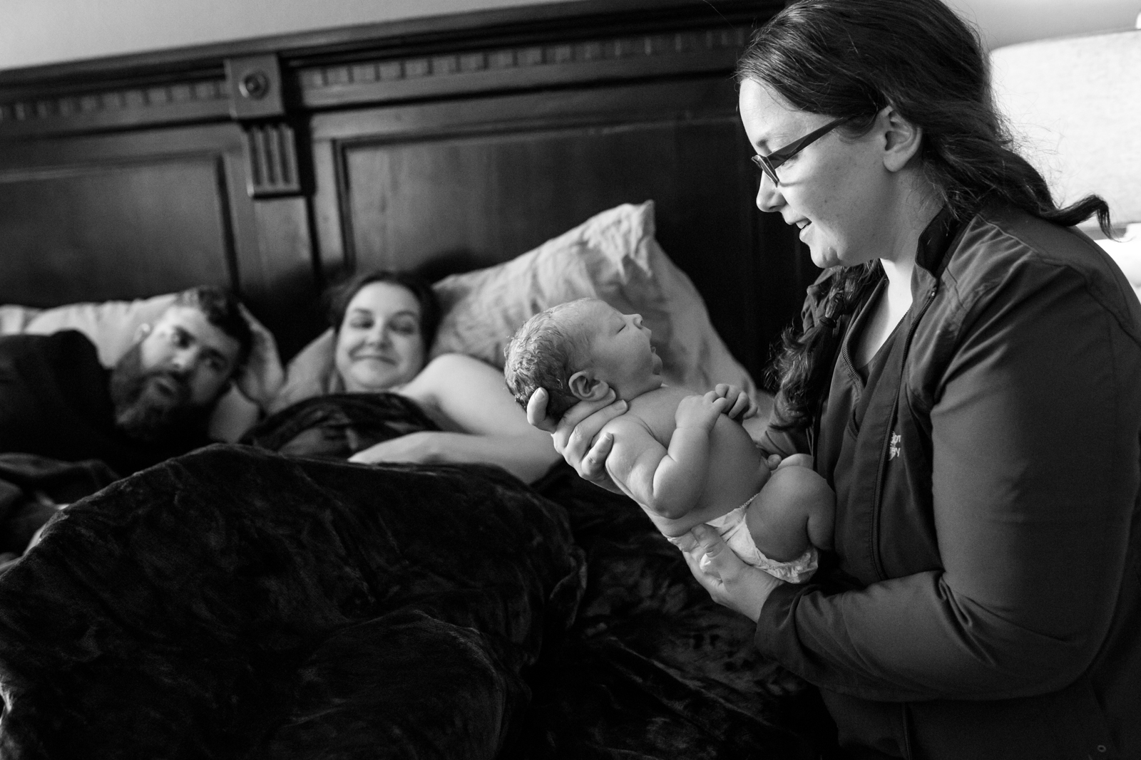 Birth Photographer Lawren Rose Photography captures a beautiful moment of a home birth midwife holding a brand new baby and smiling, while mom and dad are nearby smiling at her in prosper texas