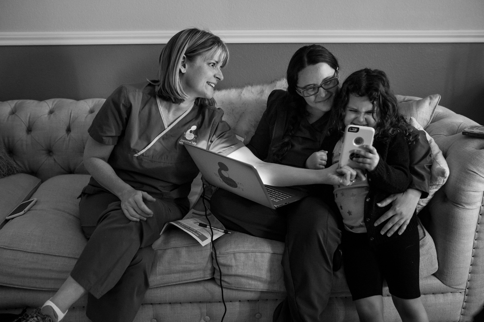 Lawren Rose Photography captures a moment between a little girl and a midwife taking a selfie just after a home birth