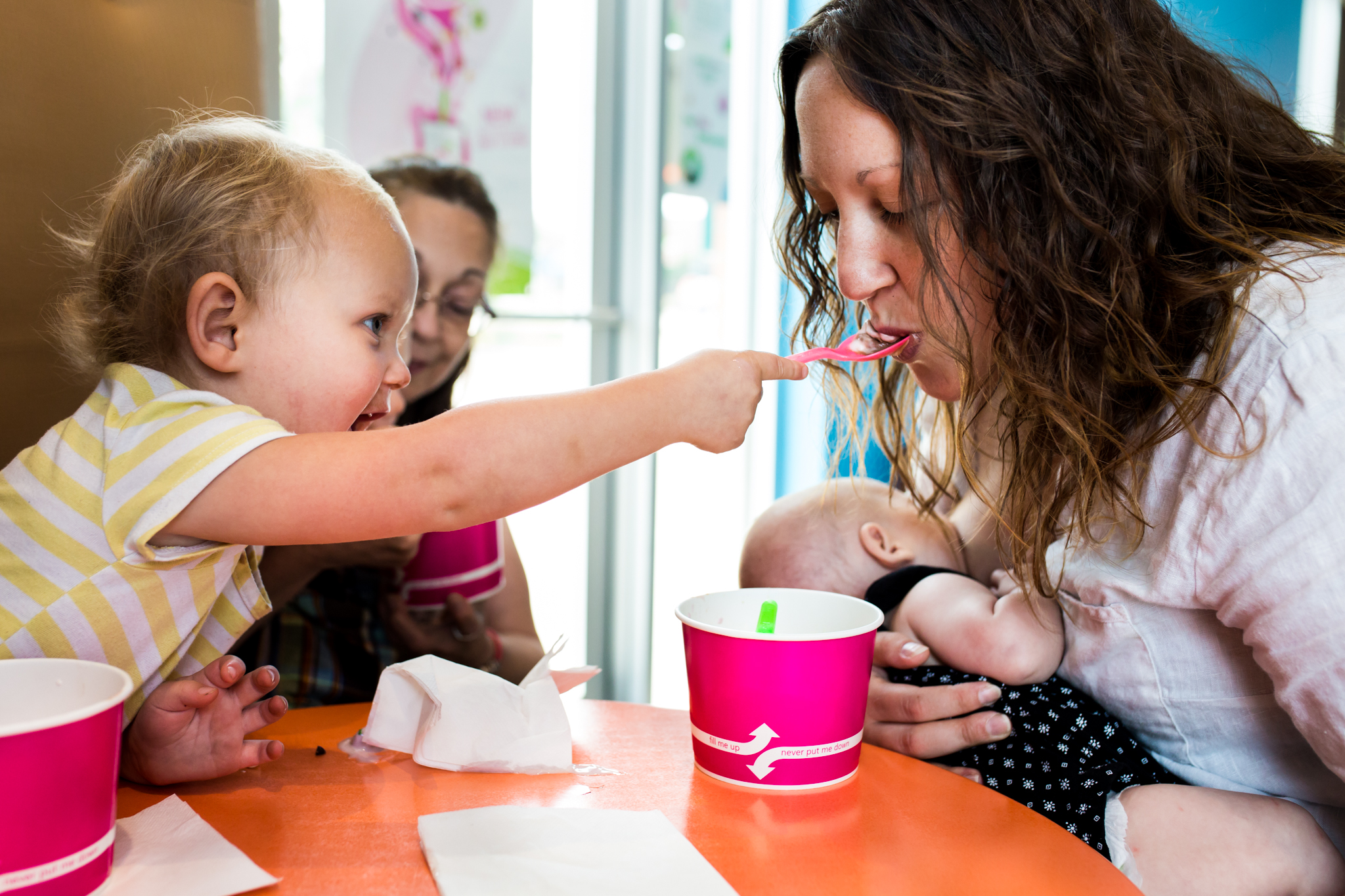 Lawren Rose Photography takes a photo of a family out eating frozen yogurt and the 2 year old daughter spoon feeds her Mom while her Mom is breastfeeding her newborn