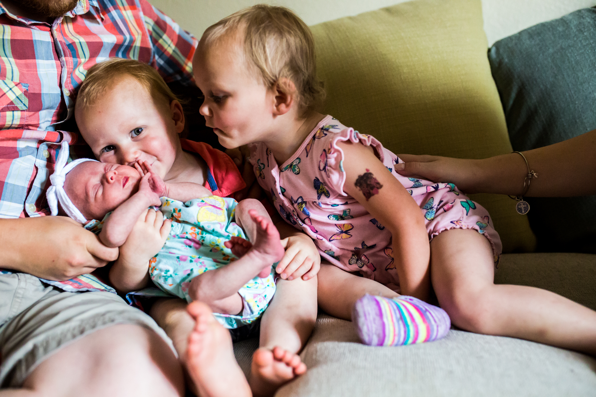 Lawren Rose Photography, a dallas family photographer and maternity photographer, takes a picture of twin brother and sister kissing their newborn baby sister at an in home photo session