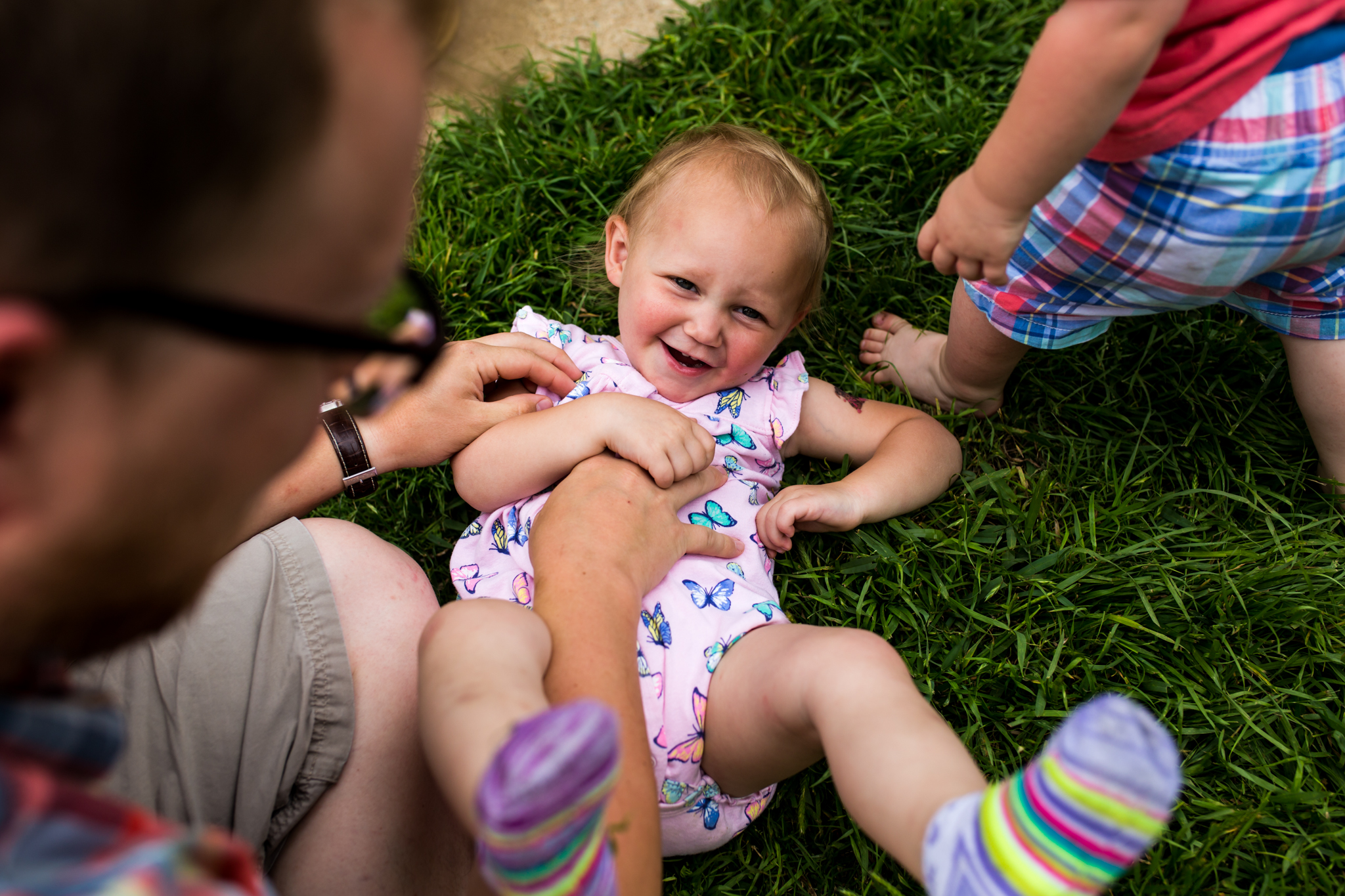 Lawren Rose Photography captures a fun moment of a father tickling his daughter in the grass while his son walks by in McKinney Texas