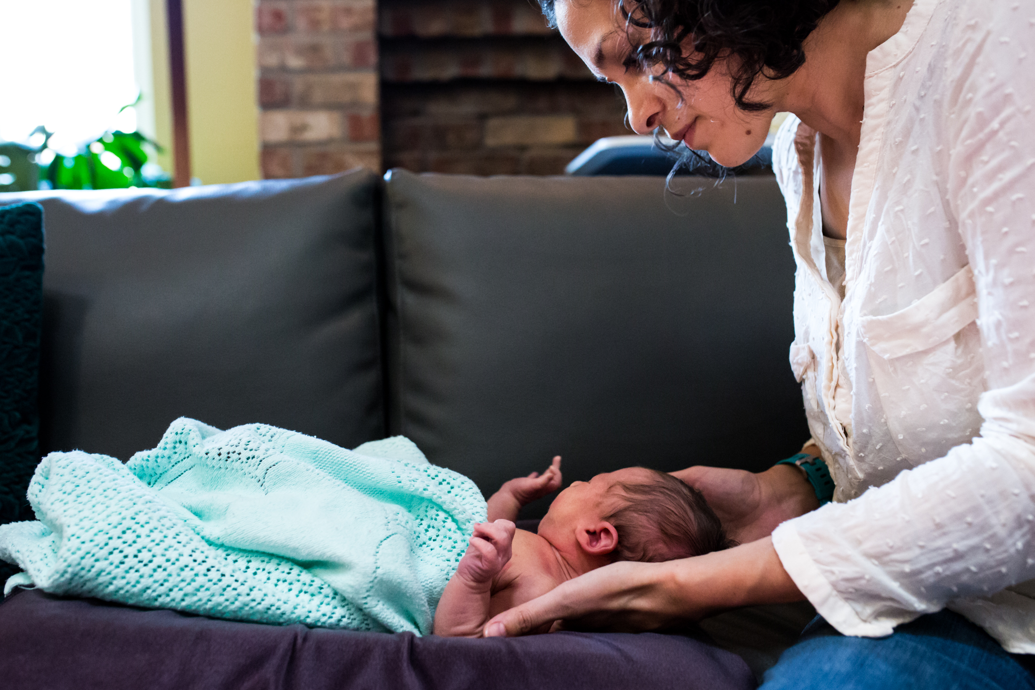 Documentary Photographer Lawren Rose Photography takes a picture from the side of a chiropractor giving a newborn baby an adjustment in a carrollon texas home