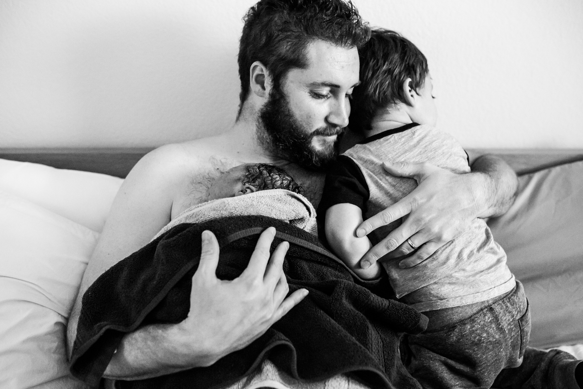 Plano Birth Photographer Lawren Rose Photography captures a moment where Dad is doing skin to skin with his newborn baby girl while also holding and hugging his toddler son