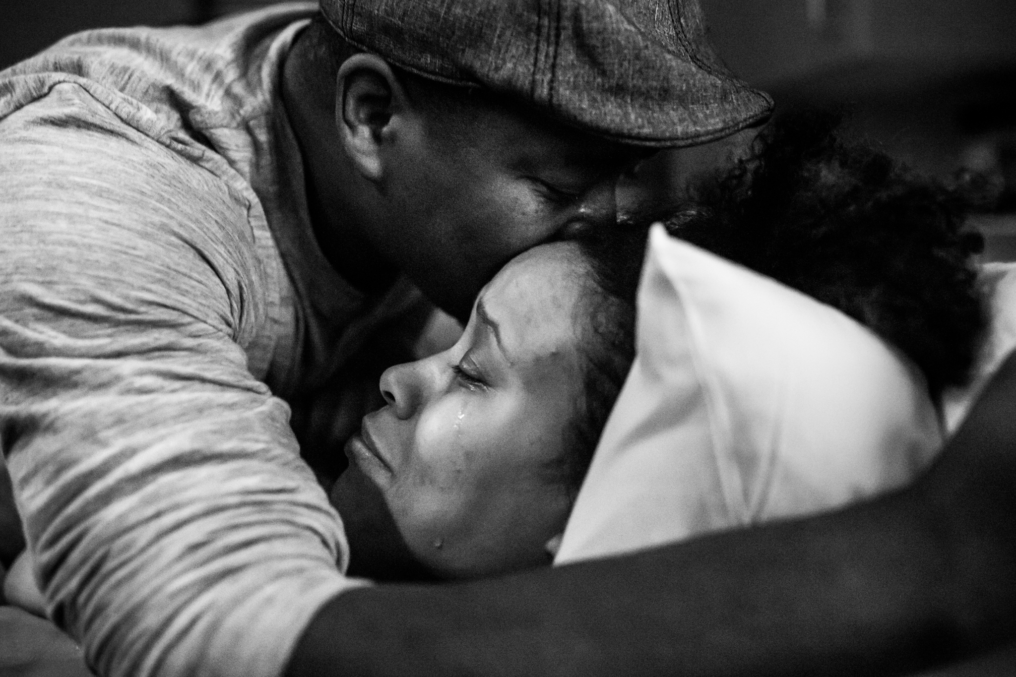 Frisco Birth Photographer Lawren Rose Photography captures a wonderful moment where a dad kisses his wifes forehead as she is shedding tears of joy after just succeeding in a vbac after 40 hours of labor, at Baylor Scott & White Medical Center - Centennial in frisco