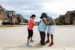 Lewisville Birth Photographer Lawren Rose Photography takes a picture of a laboring mom walking outside in the street and receiving support from her husband and doula
