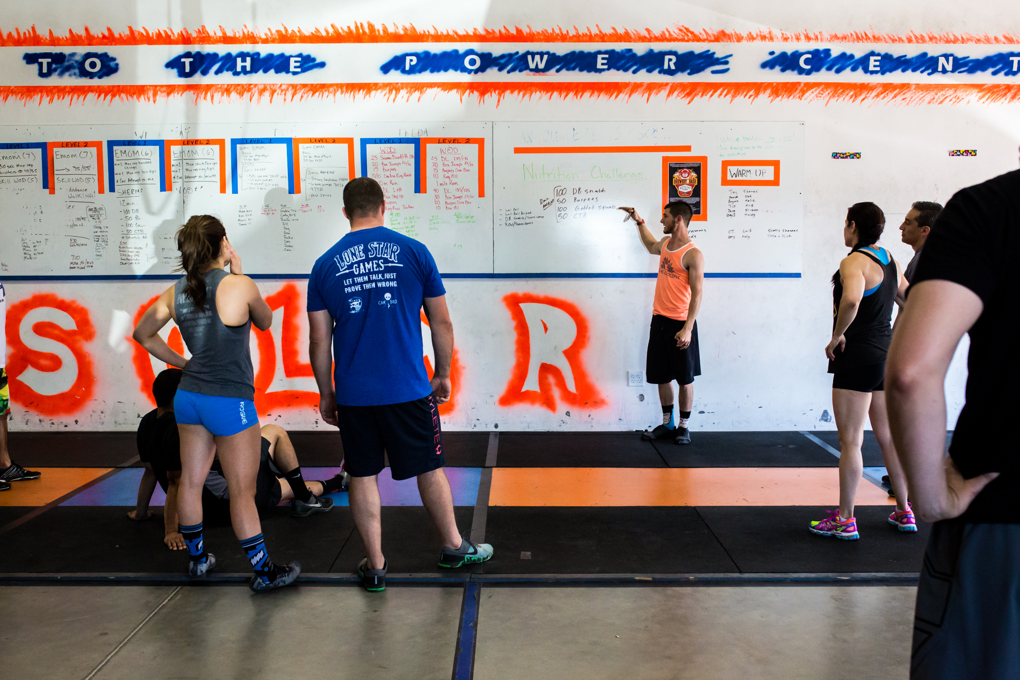 At a local crossfit gym in aubrey texas, Lawren Rose Photography sneaks a photo of the coach talking about the workout of the day