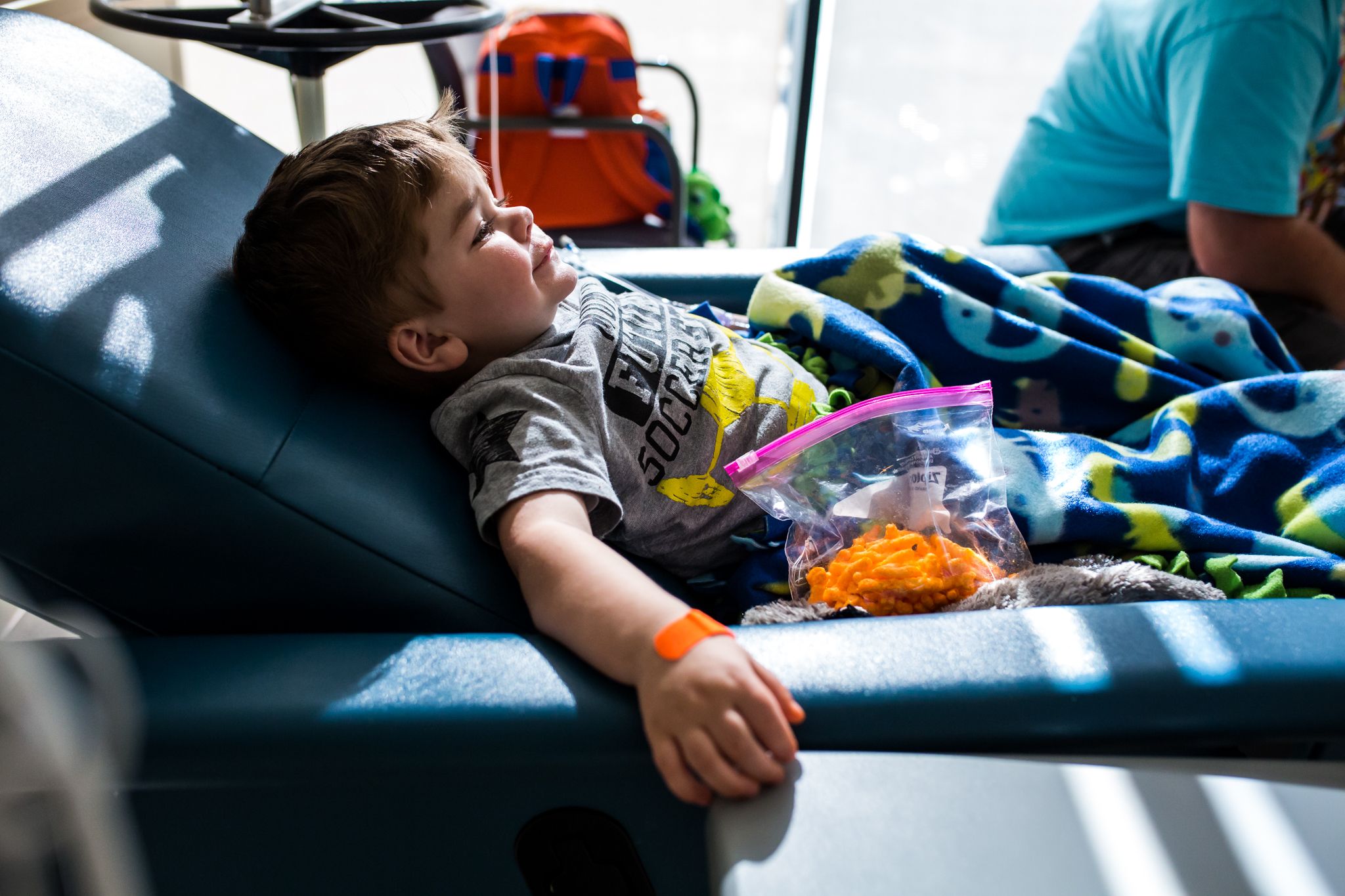 boy eating cheetos while getting an infusion