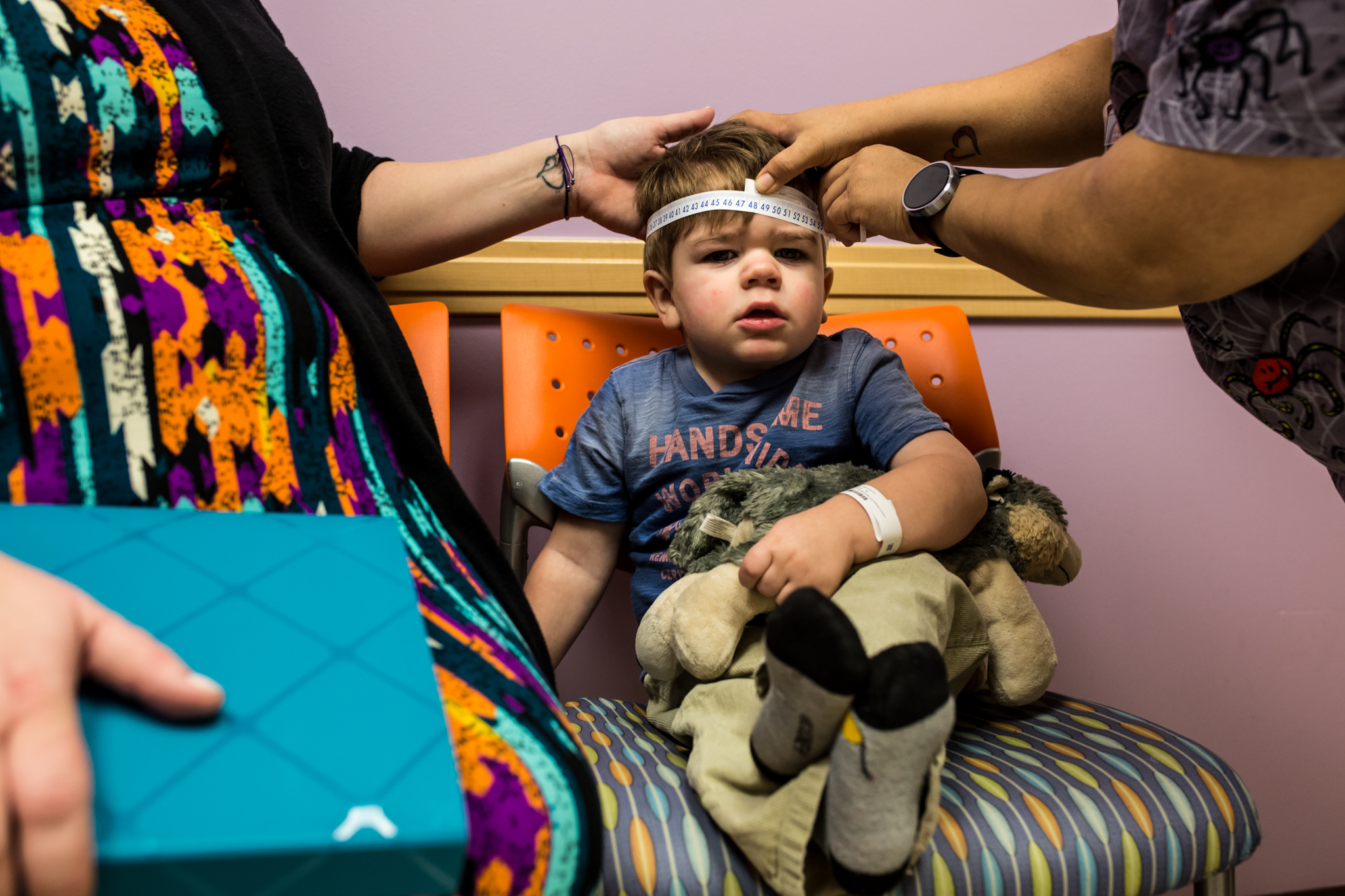 little boy getting his head measured at a doctors appointment