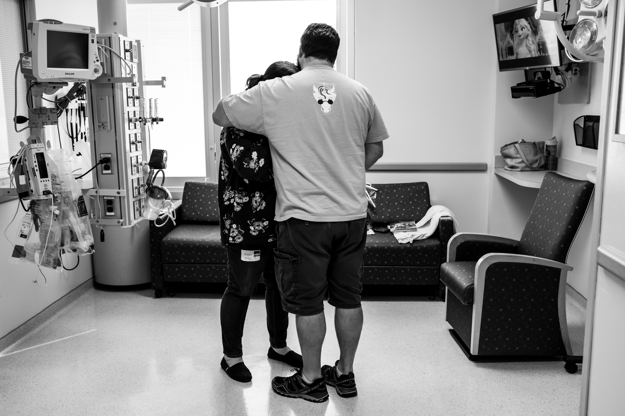 husband and wife take comfort in each other while son is in surgery