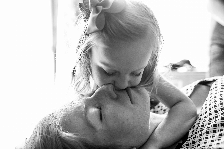 baby girl kissing her mom