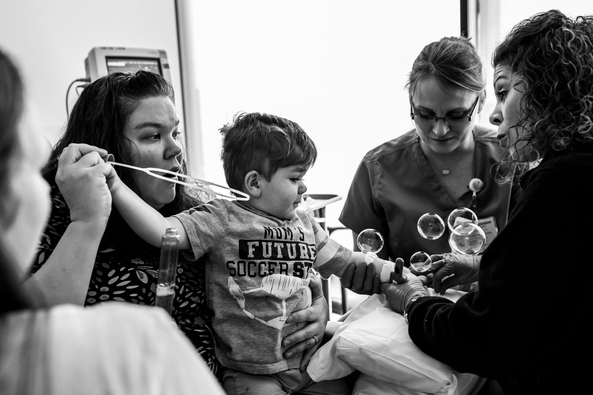 little boy blowing bubbles while getting an IV