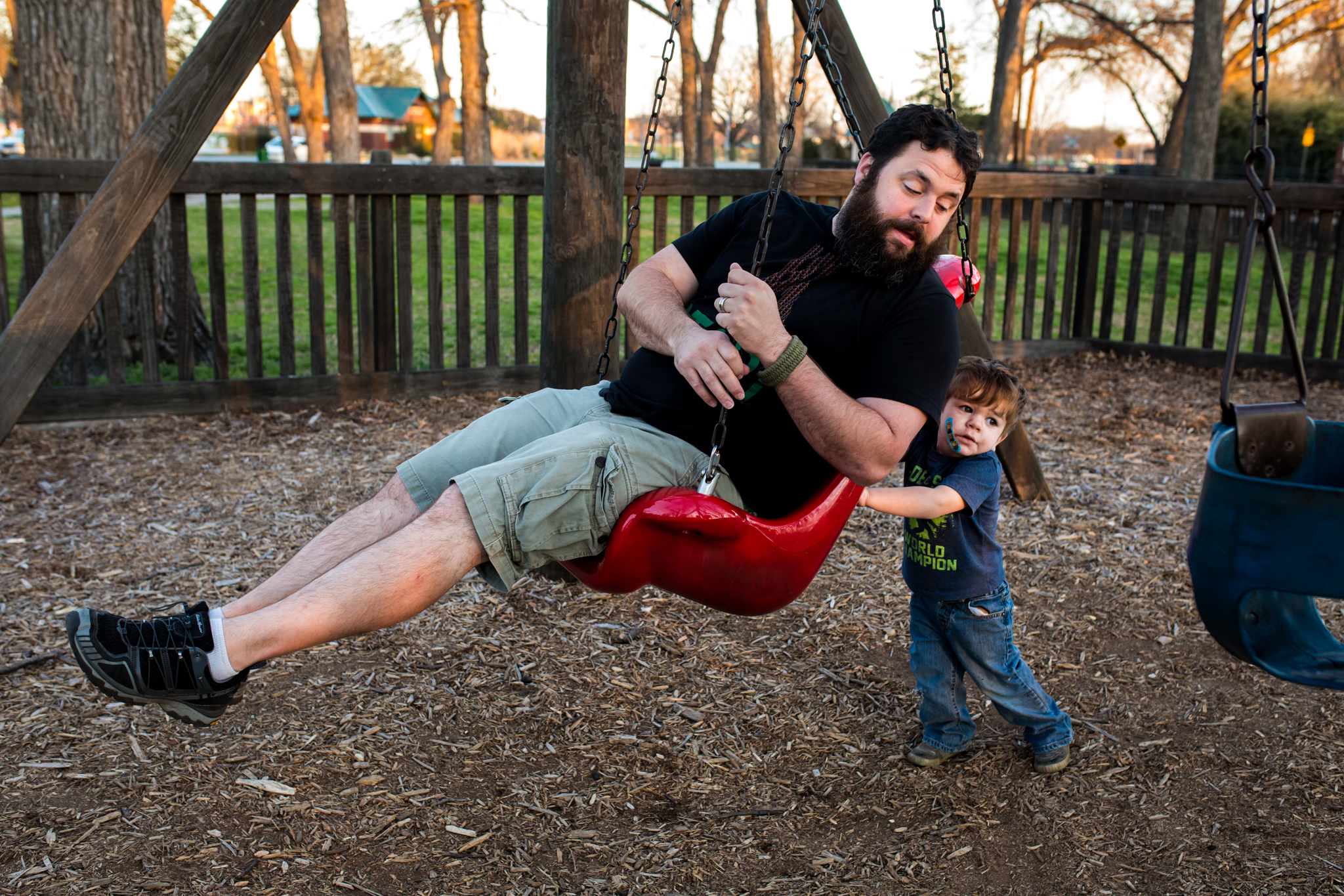 3 year old son pushing his dad on a swing set
