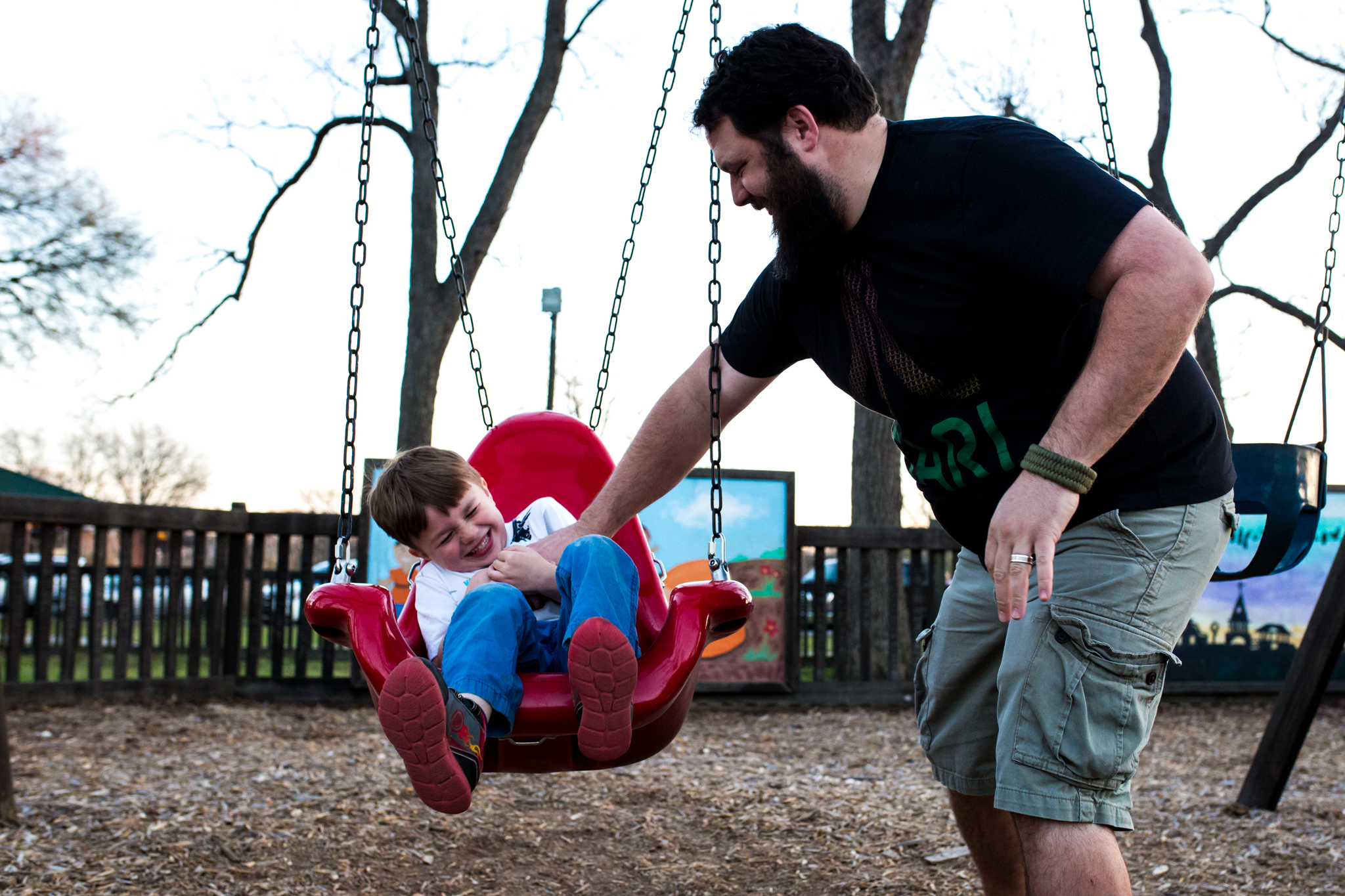 father tickles his son while on a swing set