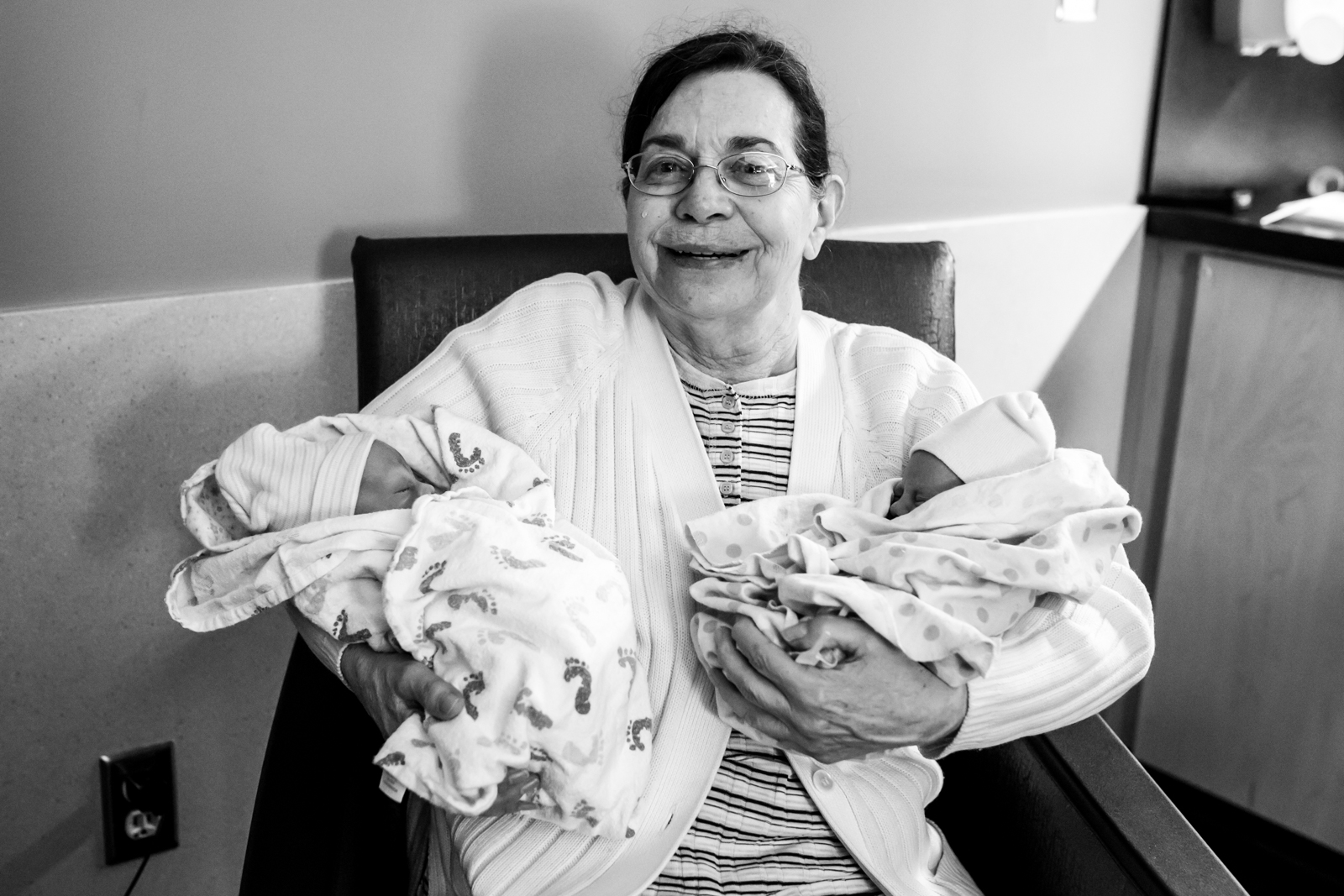 grandma holds her twin grand babies