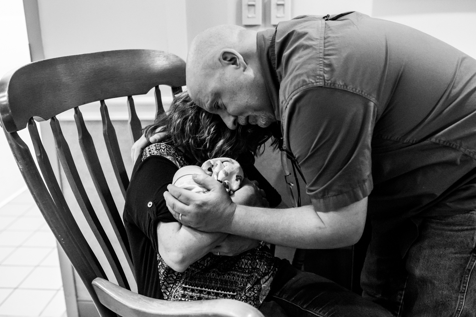 grandparents hold each other as they carry their grand baby