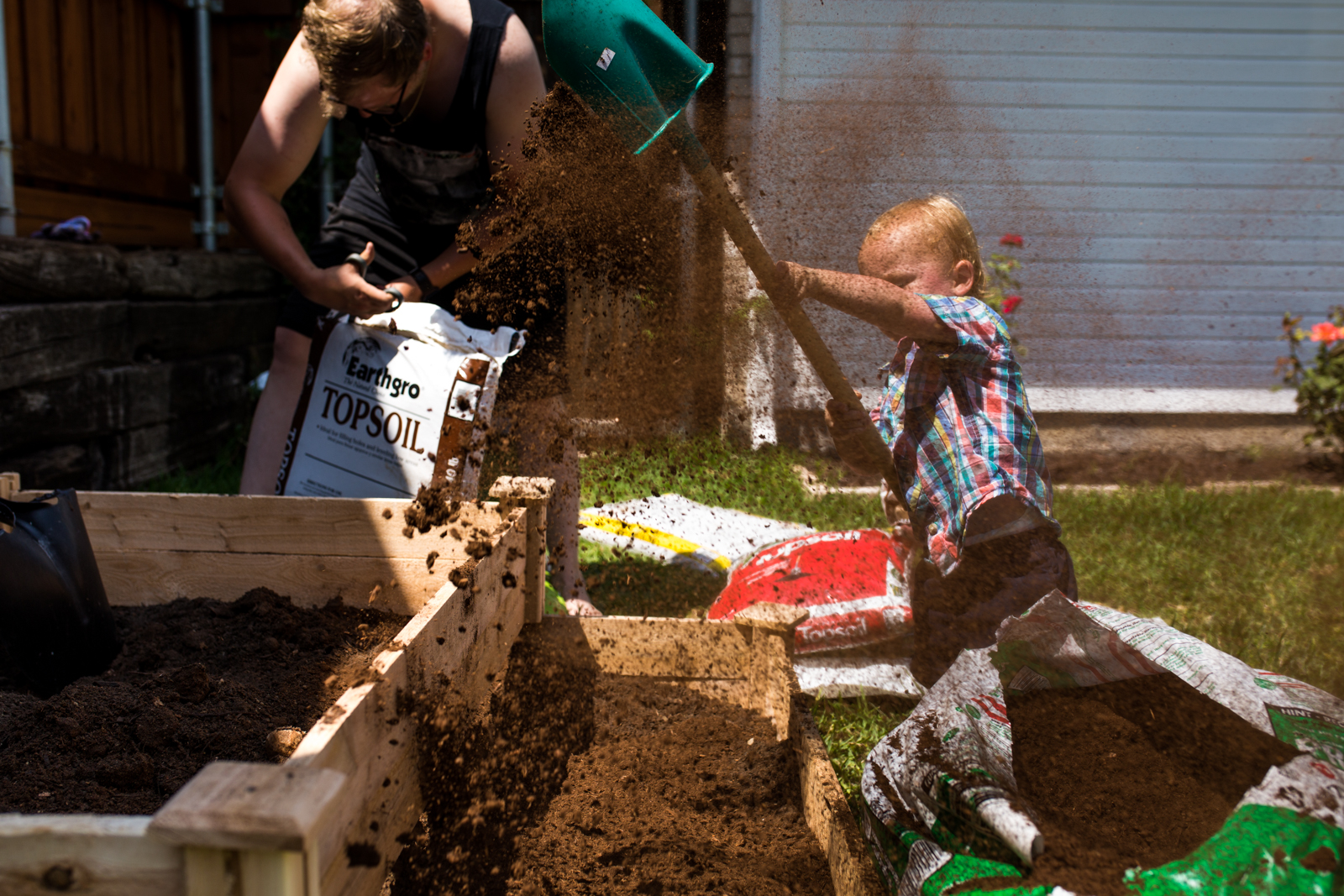 little boy trying to shovel dirt