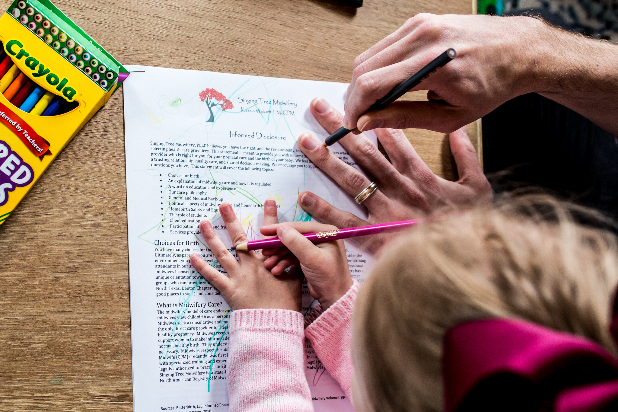 Lawren Rose Photography documents a family as they go to their first midwife appointment and takes a photo of the father coloring with their 2 year old daughter