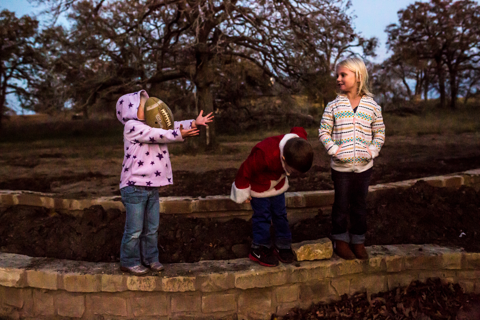 Dallas Texas Family Photographer Lawren Rose Photography captures a photo of three kids standing outside with one getting hit in the face by a football