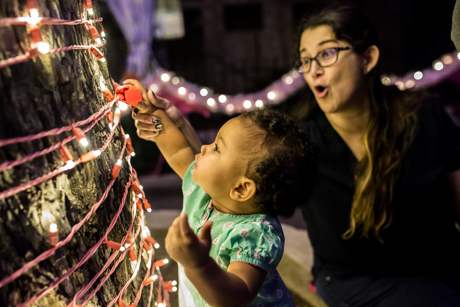 Lawren Rose Photography captures a photograph of a baby grabbing christmas lights and the Mom looking very scared
