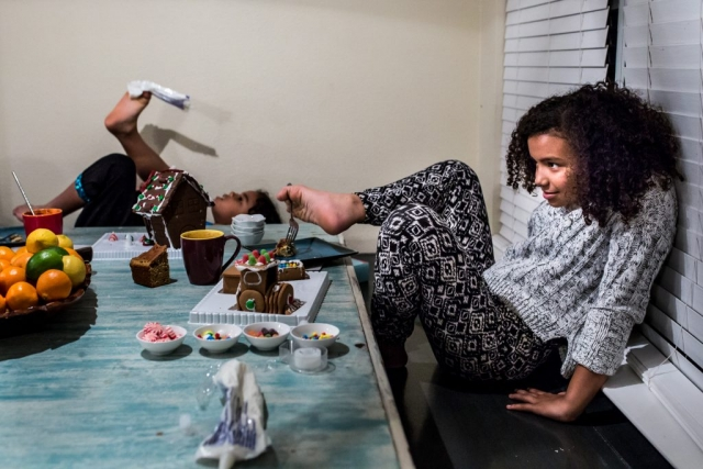 Lawren Rose Photography takes a picture of two girls sitting at their dining table using a fork with their feet