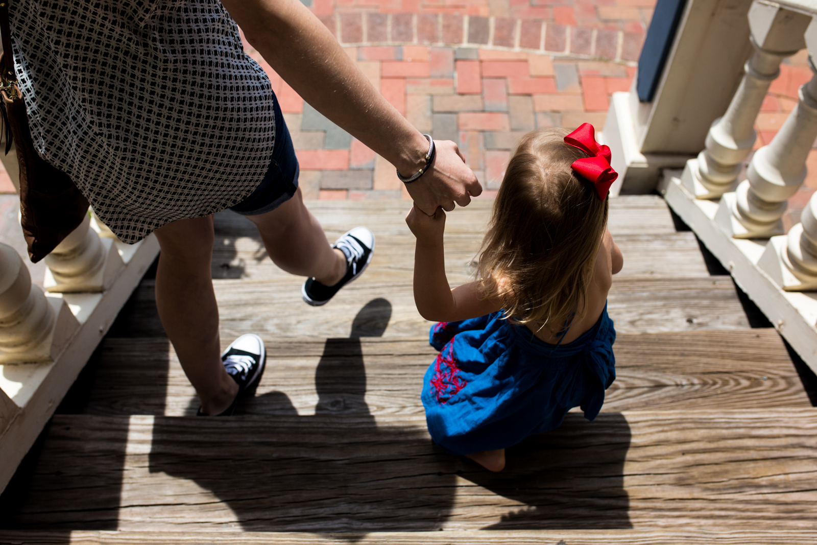 A picture taken by Lawren Rose Photography in Dallas Texas of a Mom holding her daughters hand while walking down the steps outside of the Next in Addison