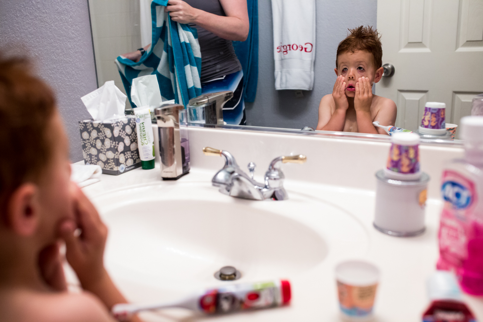 Lawren Rose Photography takes a funny photo during a maternity session of a little boy making goofy faces at himself in the bathroom mirror in mckinney texas