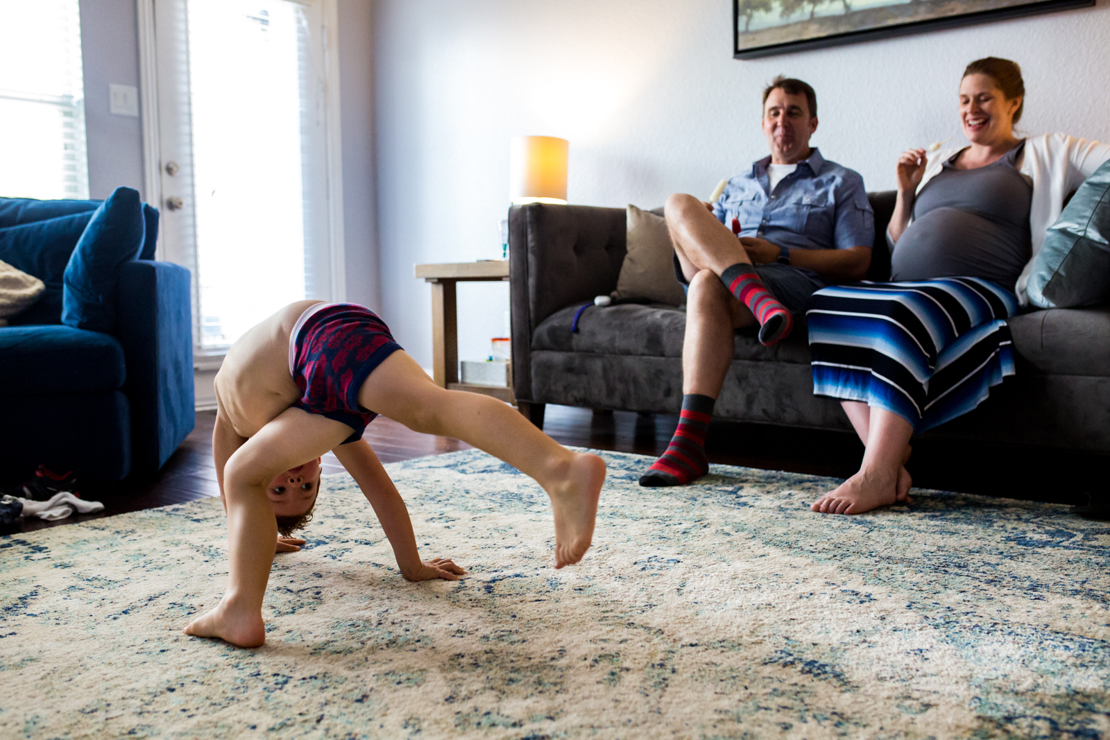 Maternity photographer Lawren Rose Photography captures a funny moment of a 4 year old boy throwing himself all over the living room dancing while his mom and dad sit back and laugh in McKinney Texas