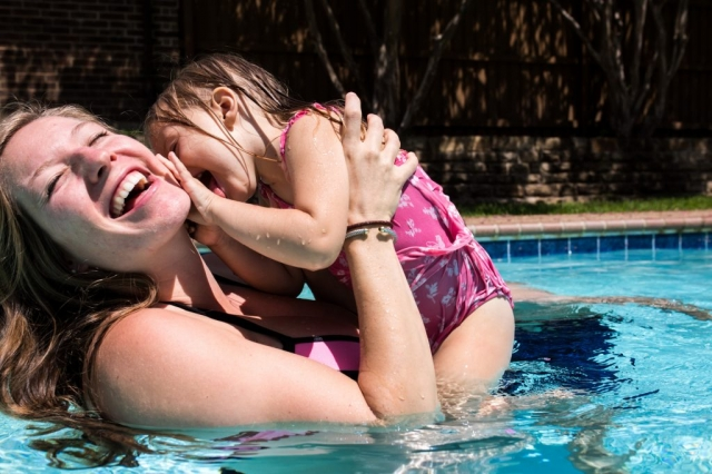 Lawren Rose Photography captures a funny moment when a Mom is getting her face licked by her daughter while swimming in a pool
