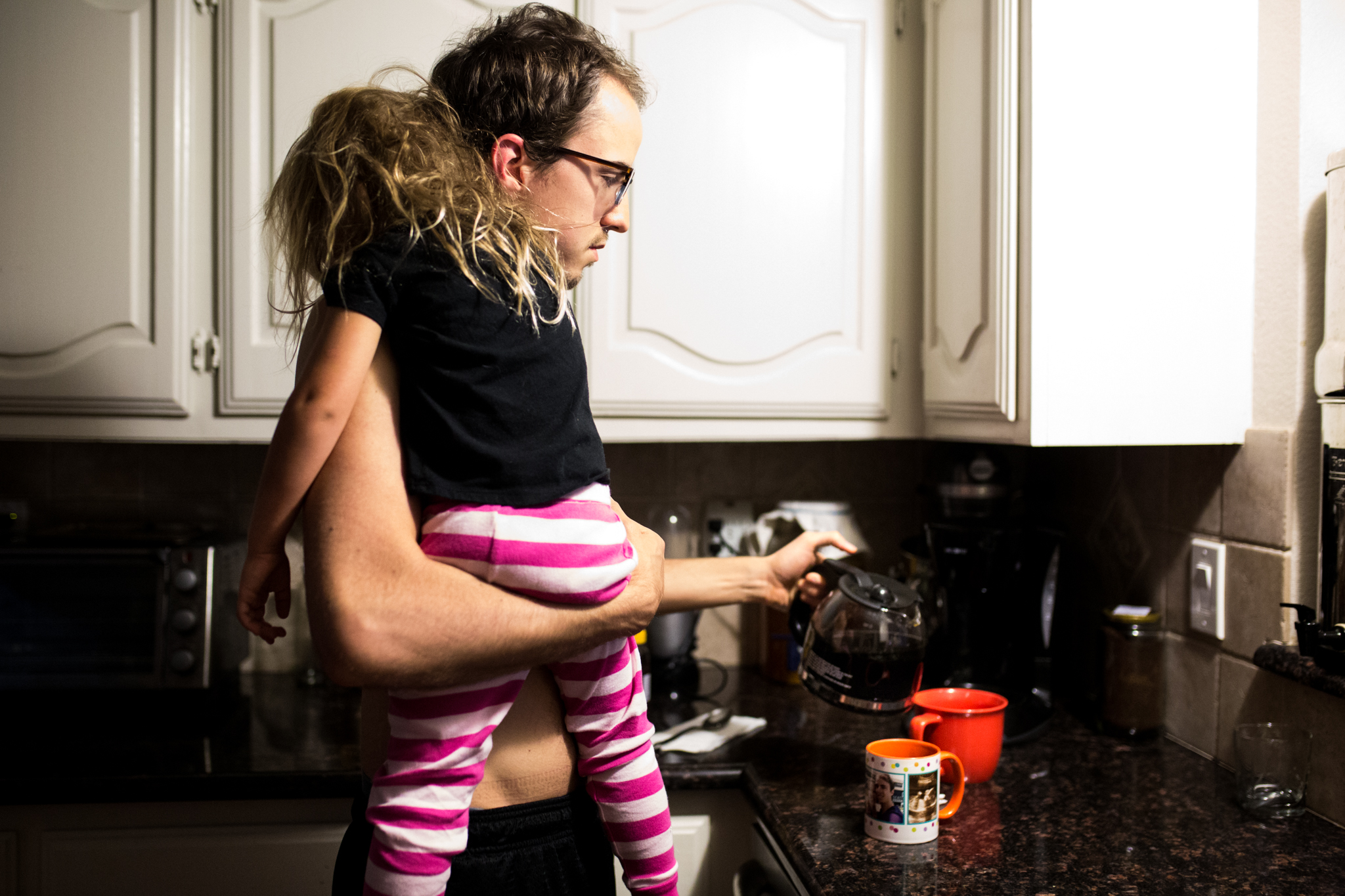 Dallas photographer Lawren Rose Photography captures a photograph of a dad holding his daughter in his arms while pouring a cup of coffee super early in the morning during a Day In The Life session