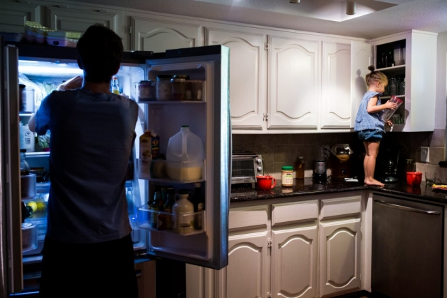 Lawren Rose Photography sneaks a picture during a Day In The Life session in Farmers Branch, Texas of a little girl standing on the kitchen countertop digging in the cabinet while the dad is digging in the fridge not paying attention