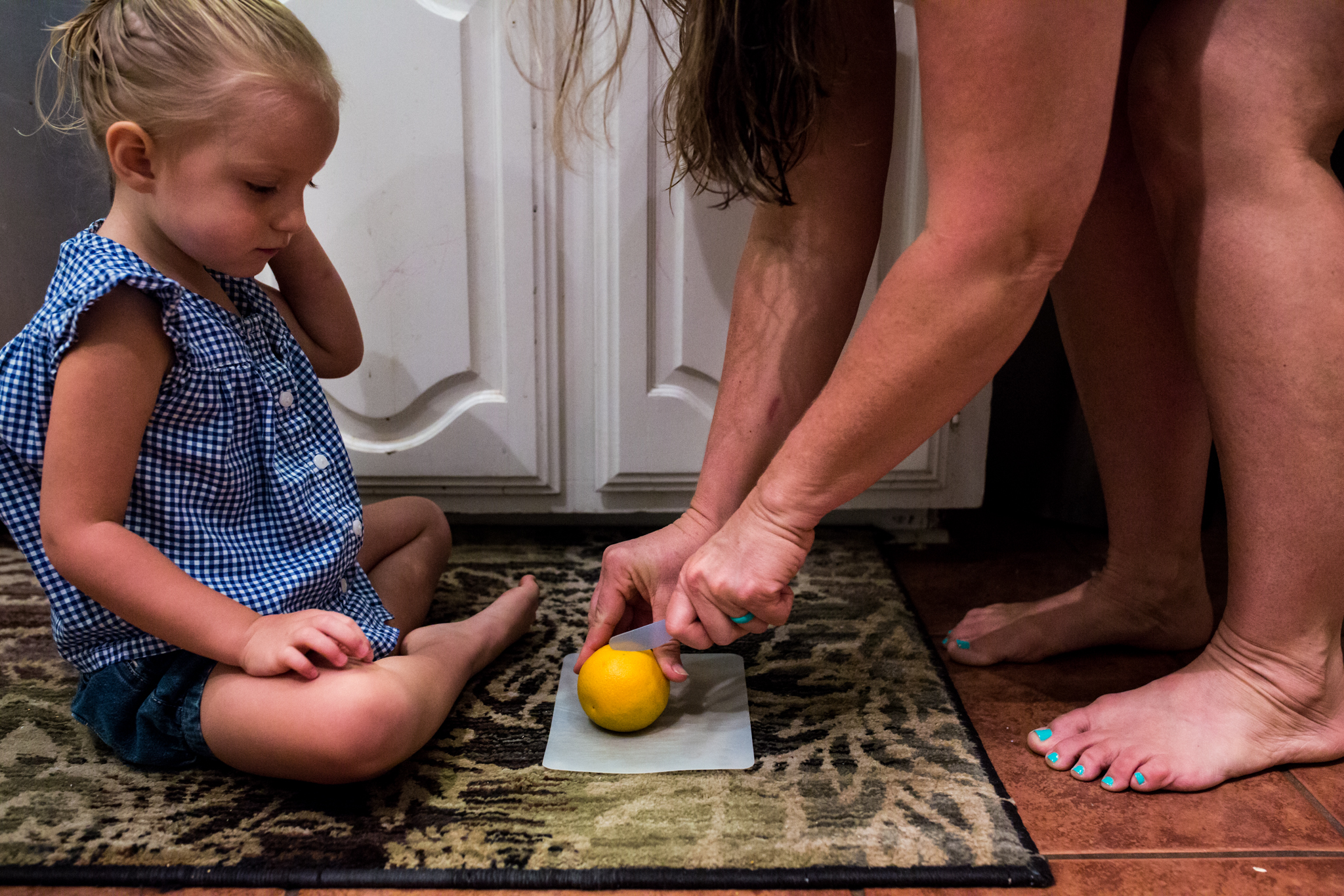 During an in-home newborn session, Lawren Rose Photography takes a photo of grandma cutting her granddaughter an orange on a cutting board on the floor