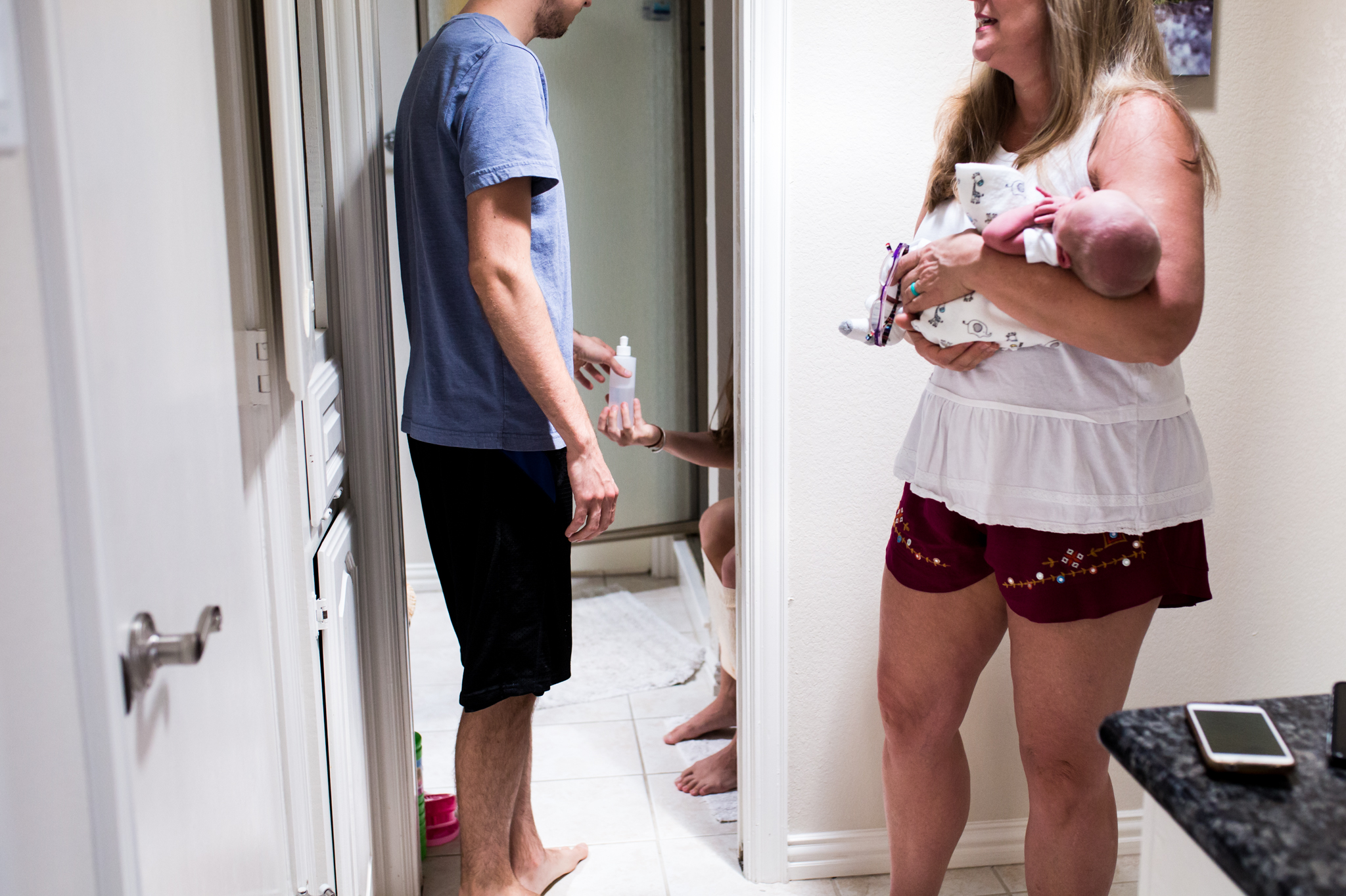 Lawren Rose Photography captures a personal moment during an in-home postpartum session where the grandma is holding a 3 day old boy while dad is handing mom a peri bottle while shes sitting on the toilet