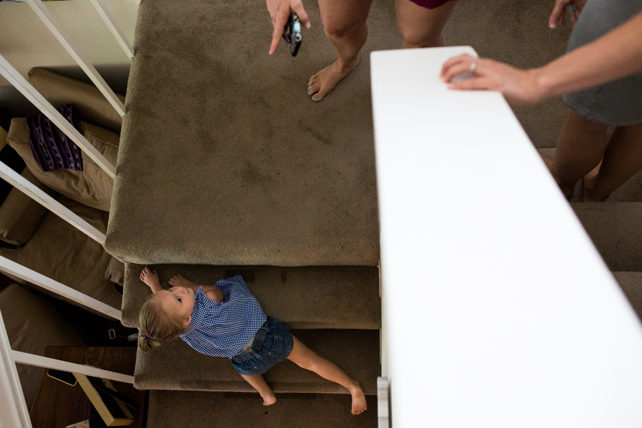 Lawren Rose Photography captures a funny moment where a little girl is going down the stairs backwards and her moms hand is pointing at her during a Day In The Life session in Farmers Branch, Texas