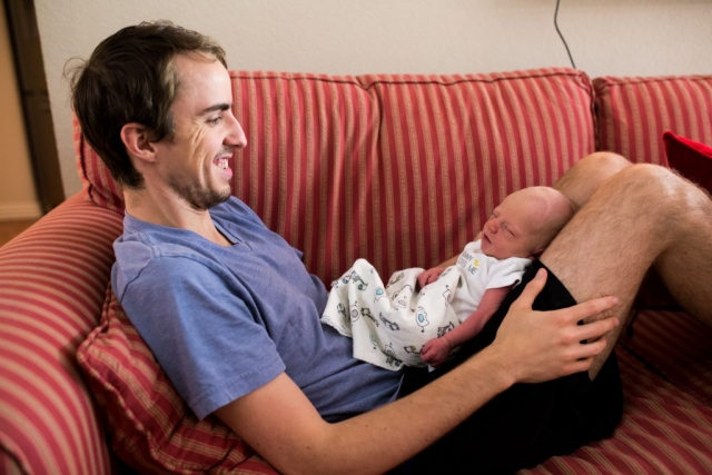 Lawren Rose Photography takes a photo of a sweet moment where a day is lounging on the couch with his 3 day old son resting up on his knees as he admires his son with a huge smile