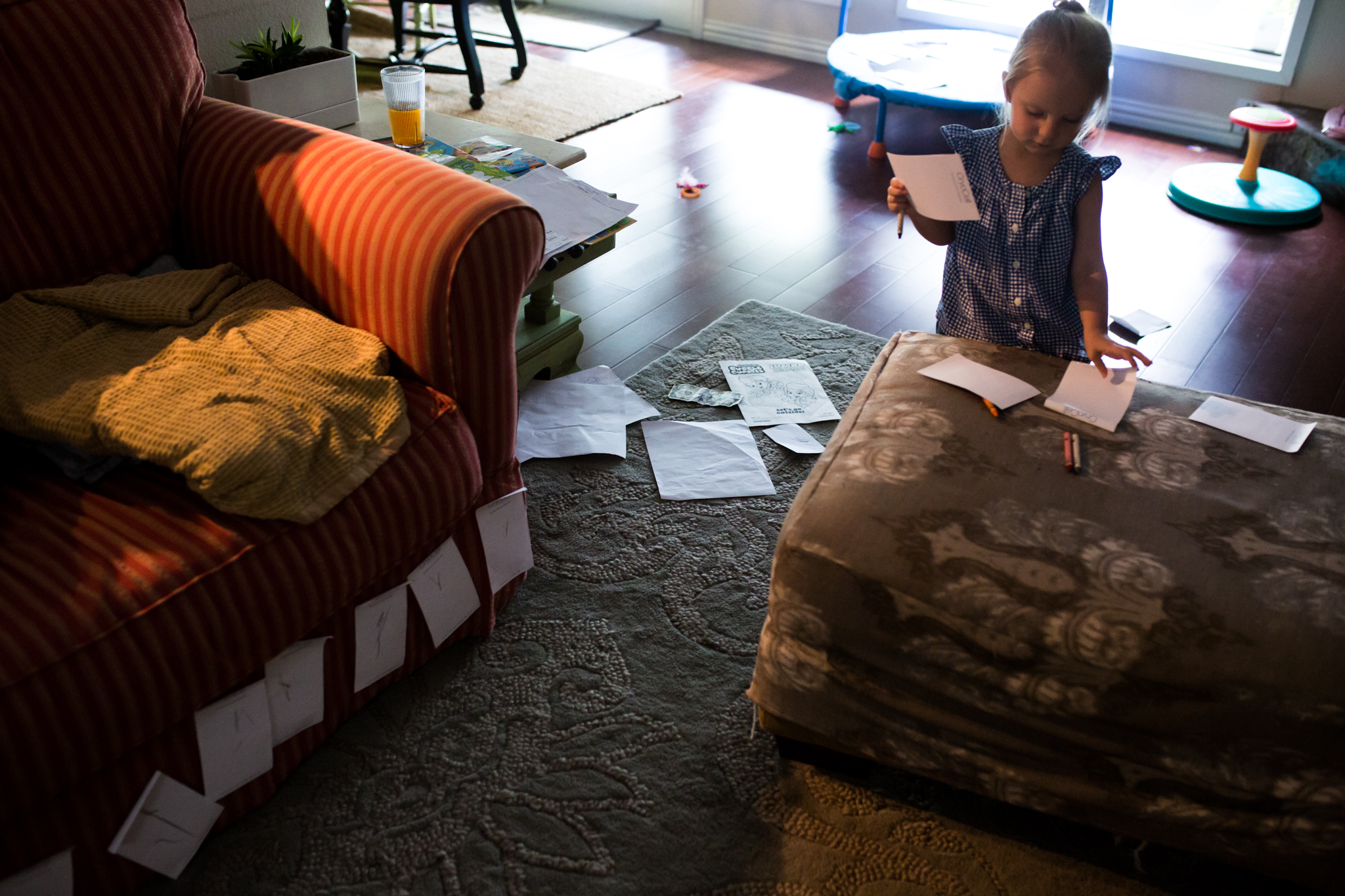Lawren Rose Photography takes a picture of a little girl sticking paper all over the living room furniture during an in-home family session in farmers branch texas