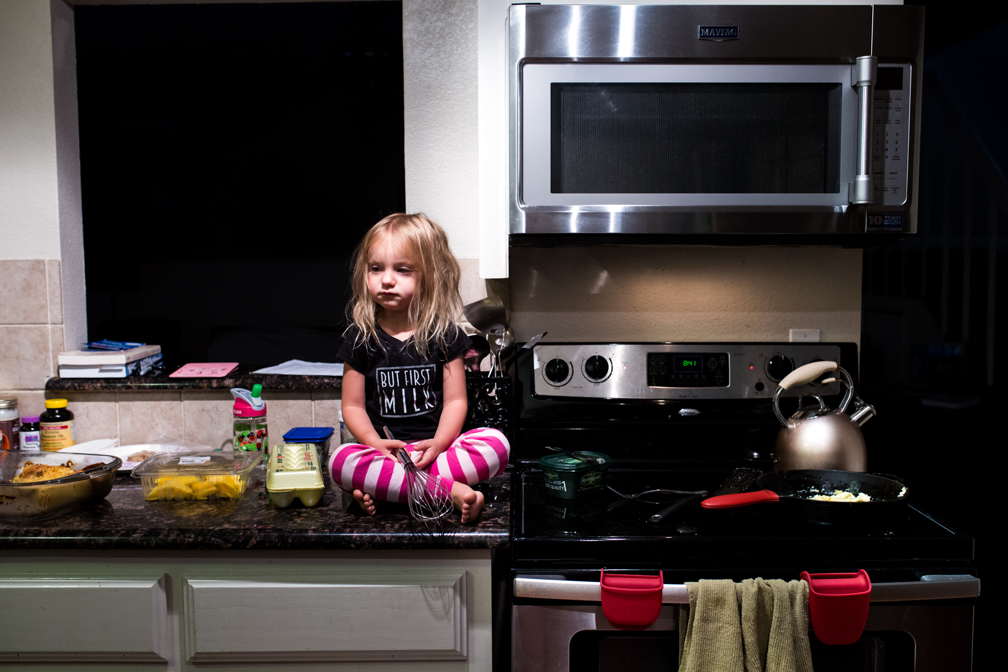 A little girl sits on the kitchen countertop waiting for her dad to finish cooking breakfast super early in the morning during a Day In The Life Session in Farmers Branch Texas
