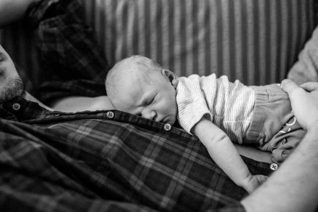 Lawren Rose Photography takes a picture during an in home newborn session of a newborn baby laying on his dad's chest in dallas texas