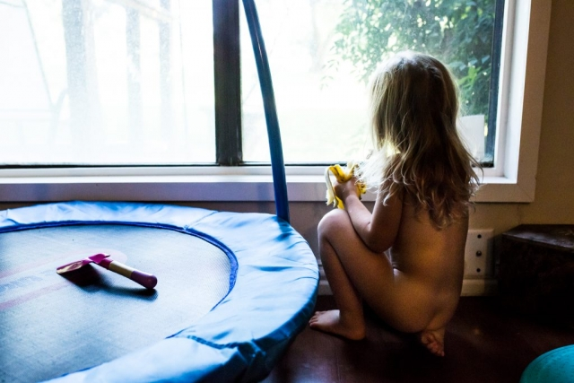 Lawren Rose Photography takes a unique photo of a little girl sitting on her foot naked eating a banana while looking out the window during an in-home documentary family photography session in dallas texas