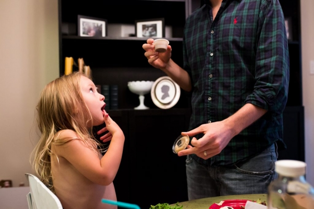 Lawren Rose Photography takes a photograph of a dad letting his daughter taste salad dressing, so shes licking her finger and making a funny face, during a documentary family photography session in farmers branch