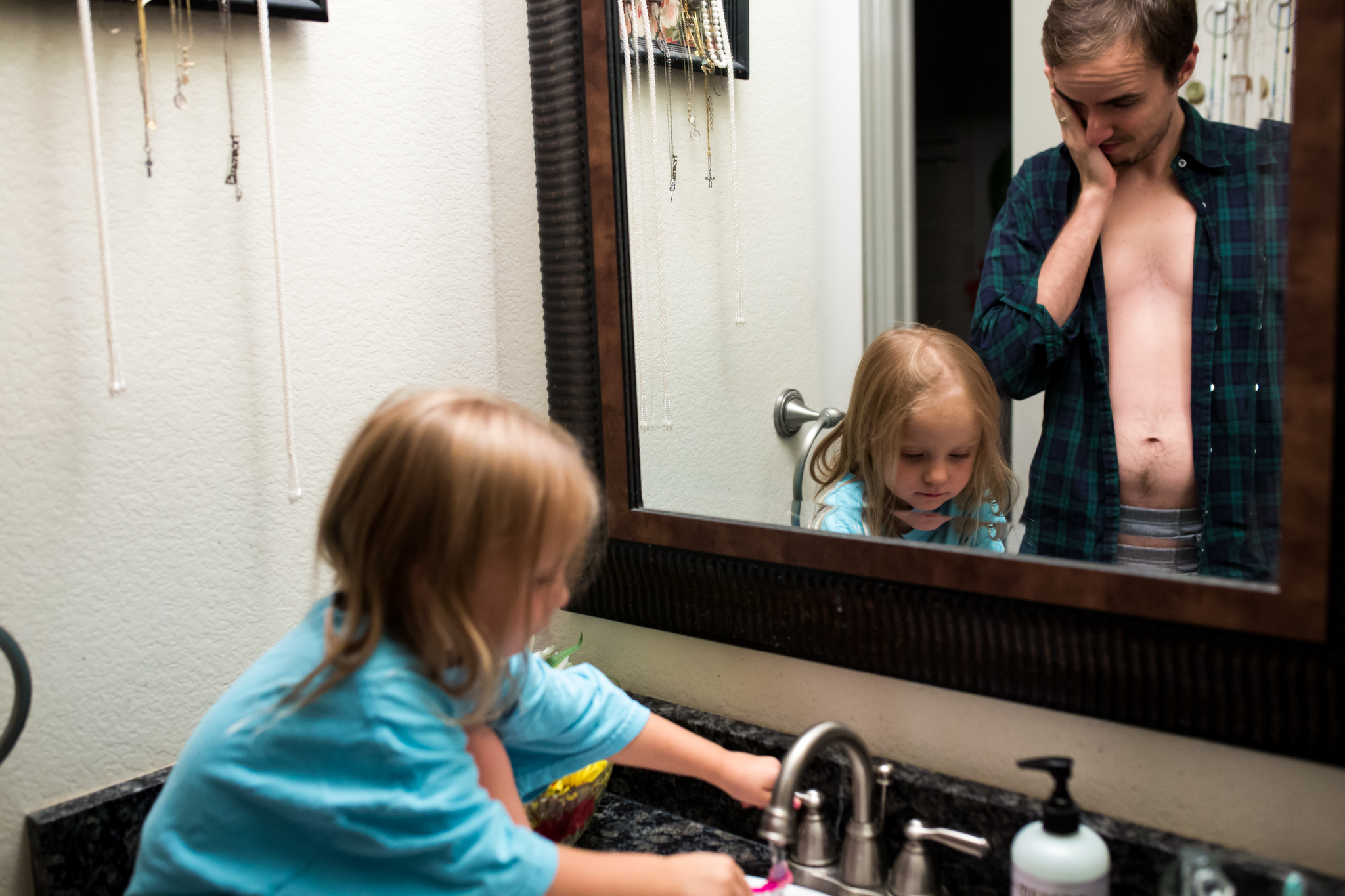 Lawren Rose Photography takes a picture of a family at the end of the day where the dad is clearly worn out as he watches his daughter brush her teeth during an in-home family photography session in farmers branch texas