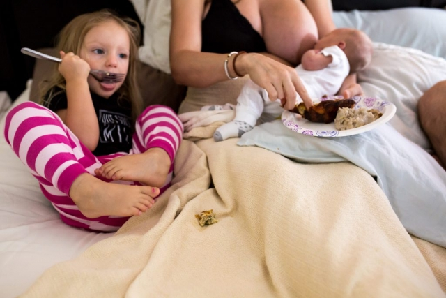 During a Day In The Life Session, Lawren Rose Photography takes a picture of a toddler playing while she eats laying in bed next to her baby brother who is nursing