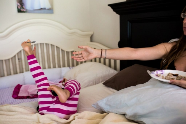 Lawren Rose Photography captures a funny moment where a daughter is holding a fork with her foot and her mom is trying to grab it from her, during a Day In The Life session in Dallas Texas