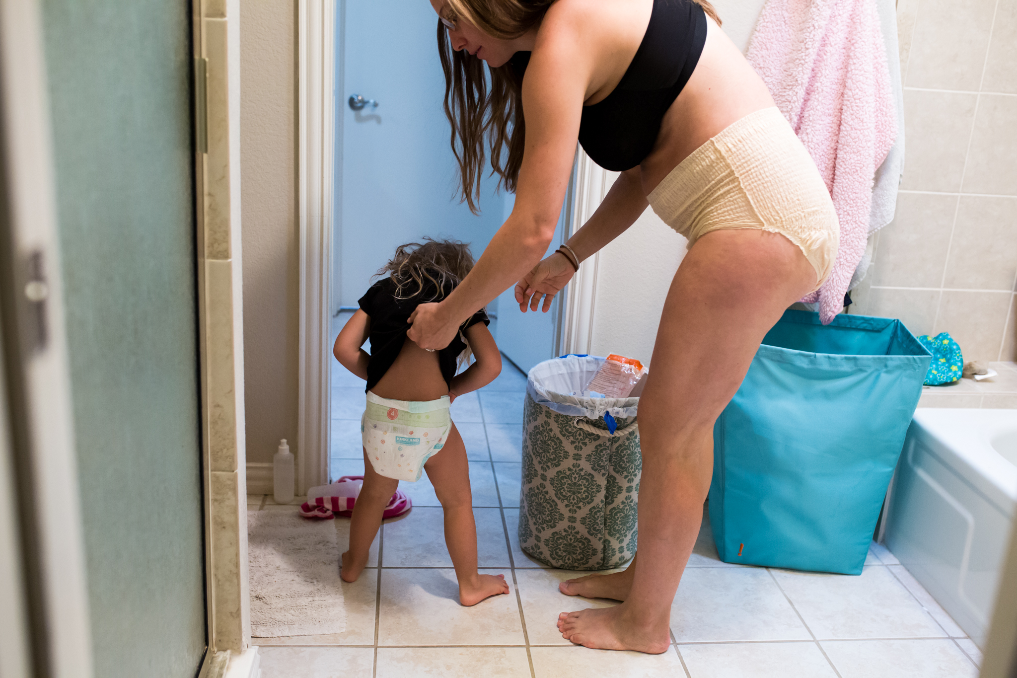 Lawren Rose Photography  takes a picture of a mom wearing depends after just having a baby in the bathroom helping her daughter take off her diaper during their Day In The Life session