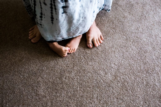 During a Day In The Life Session in Farmers Branch, texas, Lawren Rose Photography takes a picture of children toes under the same dress as Mom's toes!